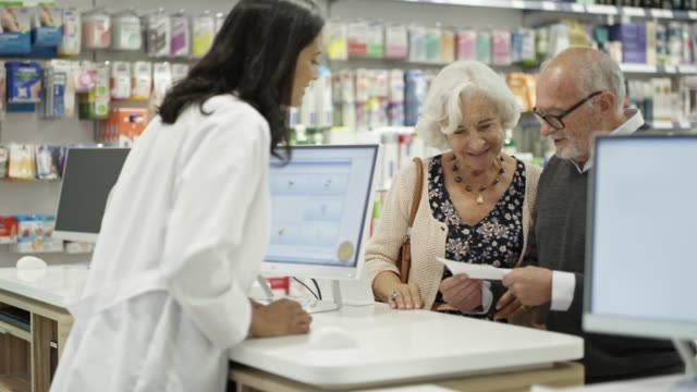 Senior couple giving prescription to pharmacist Handheld shot of elderly man and woman giving prescription to female chemist. Confident pharmacist is using computer while talking to senior couple. They are standing at checkout counter in drug store. pharmaceutical industry stock videos & royalty-free footage