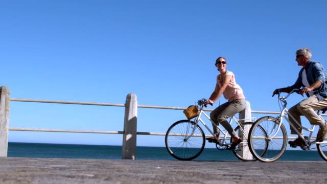 senior coppia andando in un giro in bicicletta sul molo - quarantenne video stock e b–roll