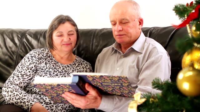 Senior couple going through photo album on Christmas video