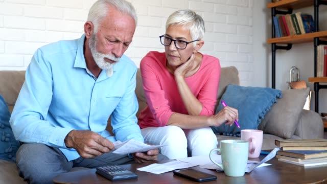 stockvideo's en b-roll-footage met senior paar hebben een harde tijd met huis financiën - overstuur