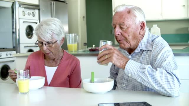 Senior Couple Having Breakfast In Kitchen Together video