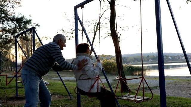Senior couple having fun on the swing video