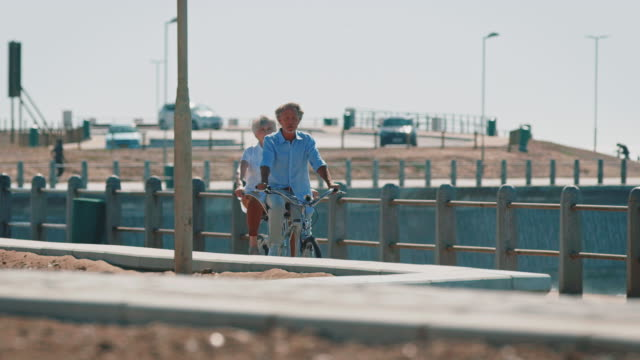 Senior couple having fun while riding tandem bikes