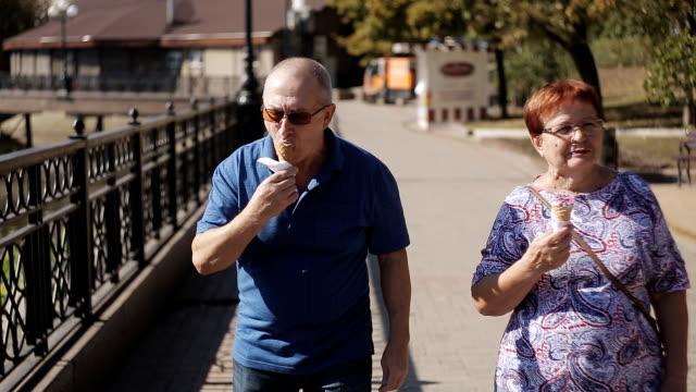 Senior couple having ice cream at promenade on a sunny day