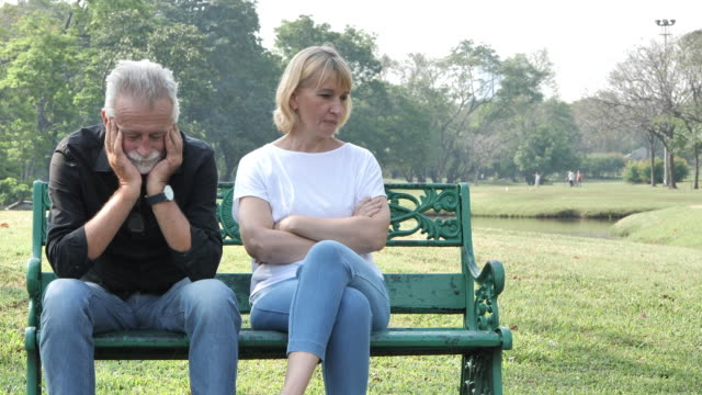 senior couple having problem, conflict, sadness, do not understand in a park. slow motion - divorzio video stock e b–roll