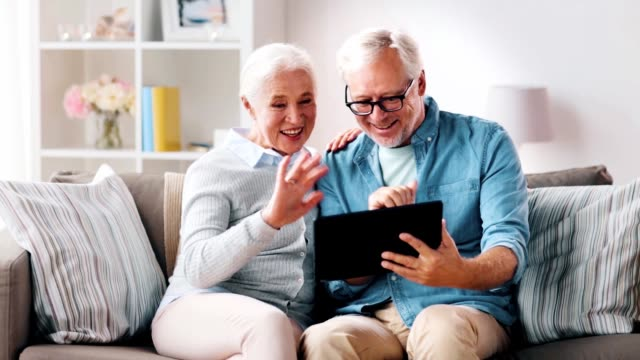 senior couple having video call on tablet computer - vídeo