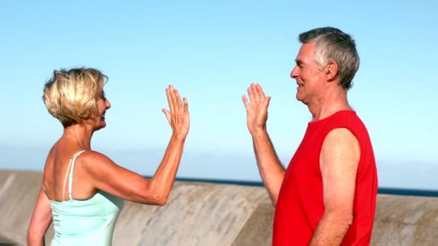vídeos de stock e filmes b-roll de casal idoso fiving alta, após corridas descontraídas ao ar livre - 55 59 anos