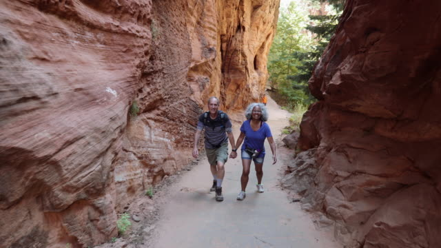 4k uhd: senior couple hiking through canyon - parco nazionale video stock e b–roll