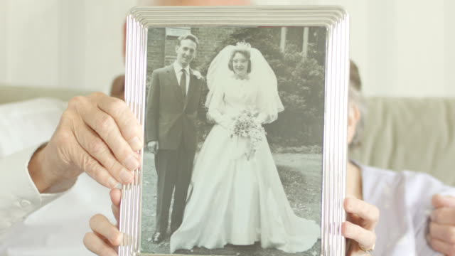 Senior couple holding up their wedding photo video