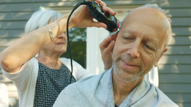 Senior couple home grooming Senior couple home grooming: woman is trimming hair on man's head. They are outdoors on the top deck of their urban home. Sunny evening in the summer during 4th of July holidays. hairstyle stock videos & royalty-free footage