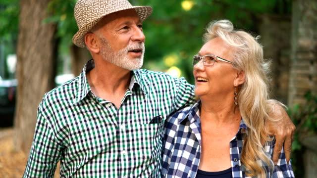 vídeos y material grabado en eventos de stock de pareja senior en un relajante paseo. - sonrisa con dientes