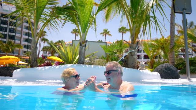 Senior couple in love hugging in swimming pool in 4K Slow motion 60fps