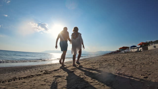 Senior couple in love walking on the beach Senior couple enjoying summer vacations. The couple is holding hands and walking on the beach on sunset. Nikon D850 falling in love stock videos & royalty-free footage