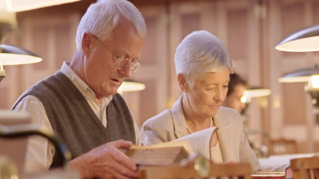LD Senior couple in the library discussing books in front of them video