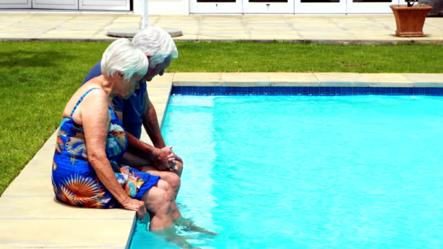 Senior couple interacting with each other at poolside