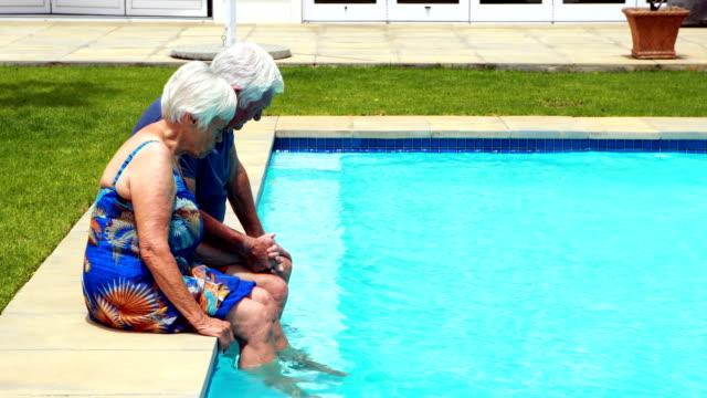 äldre par interagerar med varandra vid poolen - sarong bildbanksvideor och videomaterial från bakom kulisserna