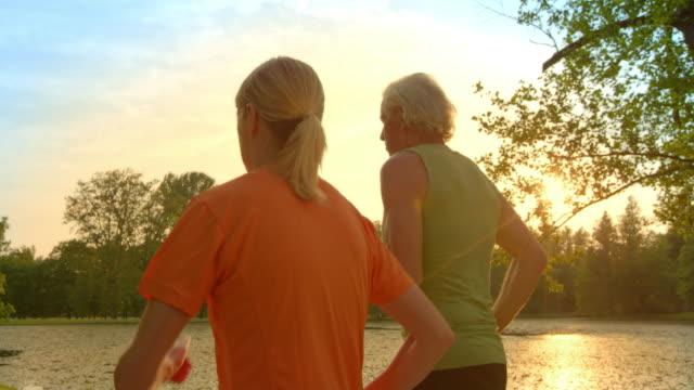 SLO MO TS Senior couple jogging along lake at sunset video