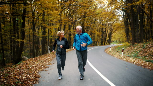 Senior couple jogging in a forest. Closeup front view of a senior couple jogging in a forest and having fun. They are running on a winding forest road, laughing and doing their healthy routine. Trees in background have turned orange and yellow and there's a lot of leaves on the side of the road. 4k video. healthy lifestyle stock videos & royalty-free footage