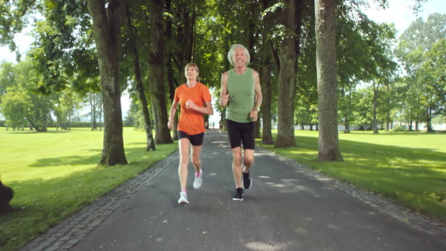 SLO MO TS Senior couple jogging through a sunny tree-lined lane Slow motion wide tracking shot of a senior man and woman jogging in the park avenue on a sunny day. tank top stock videos & royalty-free footage