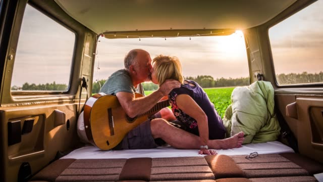 senior couple kissing in a camper van - coppia anziana video stock e b–roll