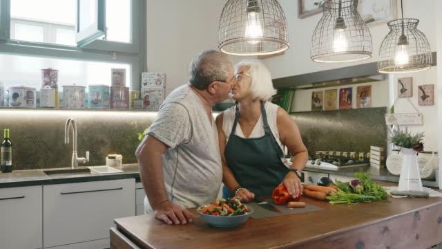 vídeos de stock, filmes e b-roll de casal sênior beijando enquanto prepara salada na cozinha da família - vegetarian meal
