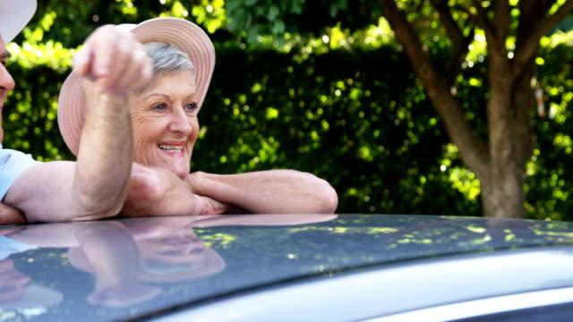 先輩カップルの車に寄りかかって - 男性 笑顔点の映像素材/bロール