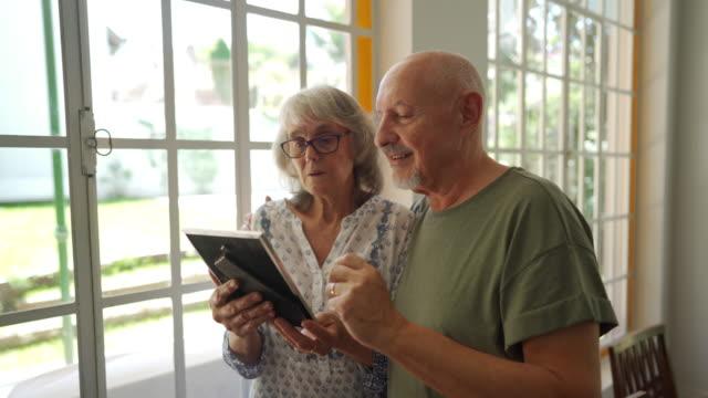 senior par tittar på bilder av sina familjer på vårdhem - fotoram bildbanksvideor och videomaterial från bakom kulisserna