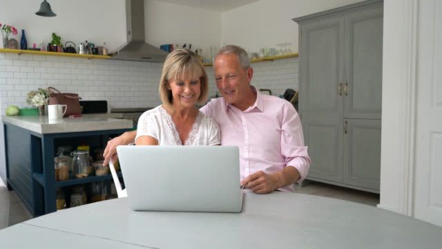 Senior couple looking at something on their laptop and talking video
