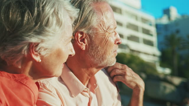senior couple looking away at beach in summer - distrarre lo sguardo video stock e b–roll