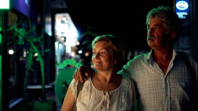vídeos de stock e filmes b-roll de senior couple looking shop window display - 55 59 anos