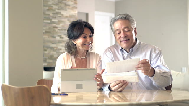 Senior couple looking through mail, paying bills A successfully retired senior couple, smiling and talking as they look through the mail, ready to pay the bills. financial bill stock videos & royalty-free footage