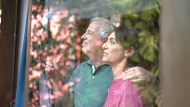 äldre par tittar genom fönstret - titta genom fönster bildbanksvideor och videomaterial från bakom kulisserna