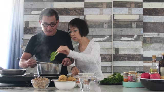 Senior couple making lunch together at home in kitchen Man stirring noodles in saucepan with chopsticks, woman adding pak choi, fresh green vegetables, healthy eating hobbies stock videos & royalty-free footage