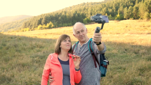 senior couple making video with smartphone gimbal - rispetto video stock e b–roll