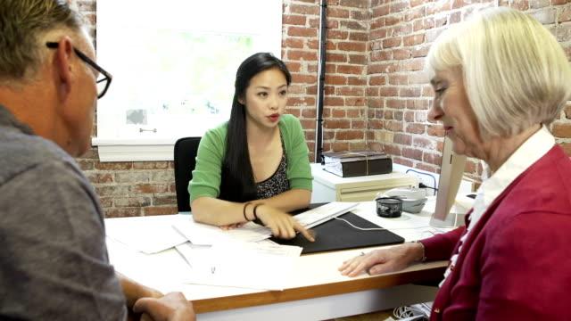 Sênior casal em reunião com um Consultor financeiro em Escritório - vídeo