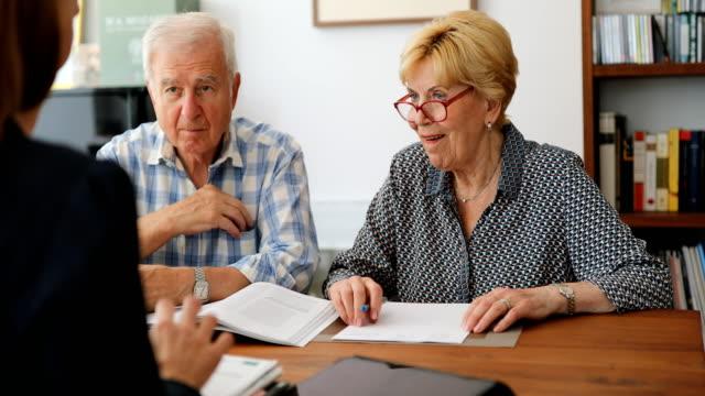 vídeos y material grabado en eventos de stock de pareja senior reunión con consultor de inversión - planificación financiera