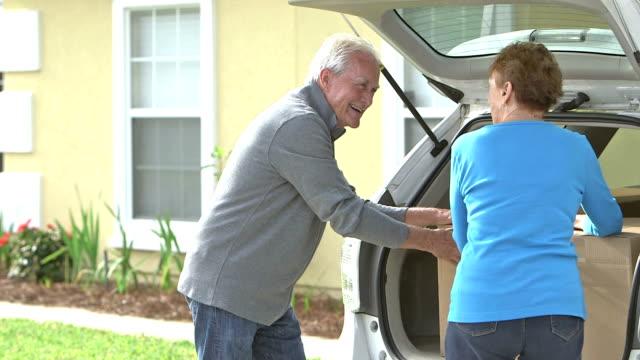 äldre par som flyttar kartong lådor från hus till bil - flyttlådor bildbanksvideor och videomaterial från bakom kulisserna