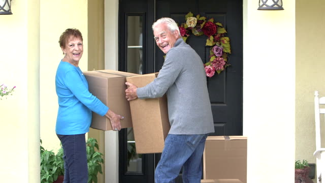 Senior couple moving cardboard boxes from house to car video