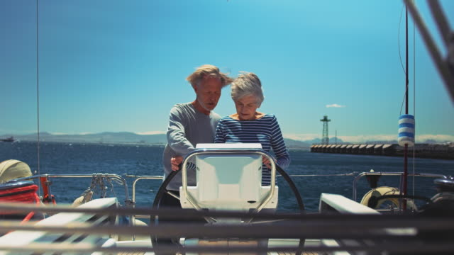 senior couple navigating in yacht during vacation Lockdown shot of senior man teaching woman to drive boat. Couple navigating in yacht during summer vacation. They are enjoying their retirement days. guidance stock videos & royalty-free footage