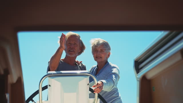 senior couple navigating on yacht during vacation - indicare la via video stock e b–roll