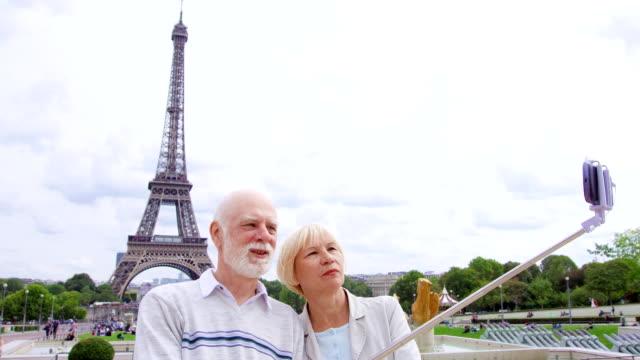 vídeos de stock, filmes e b-roll de casal sênior perto da torre eiffel, fazendo selfie. turismo na europa. vida moderna ativa após a aposentadoria - turista