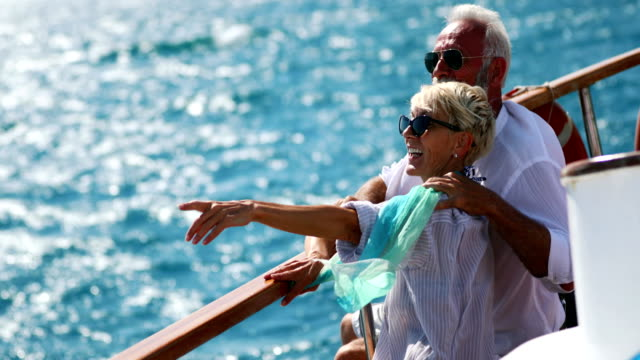 Senior couple on a sailing cruise. Closeup side view of mid 60's couple enjoying a sailing cruise during  summer vacation at seaside. They are leaning on deck railing and enjoying the view of the sea and horizon. 4k pointing stock videos & royalty-free footage