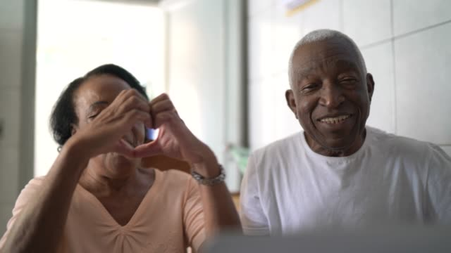 Senior couple on a video calling using laptop at home