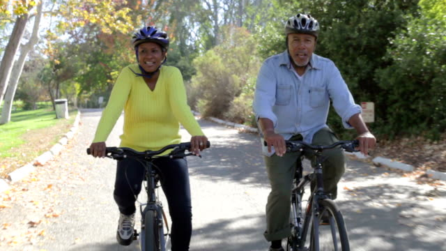 Senior Couple On Cycle Ride In Countryside Senior couple riding bikes along country road towards camera.Shot on Sony FS700 at frame rate of 25fps healthy lifestyle stock videos & royalty-free footage