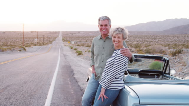 Senior couple on road trip standing by car smiling to camera Senior couple on road trip standing by car smiling to camera leaning stock videos & royalty-free footage