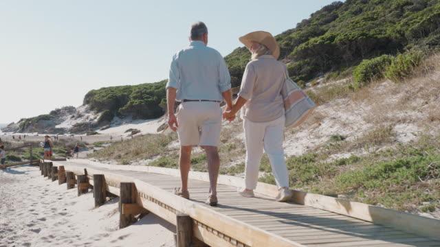 Senior Couple On Summer Vacation Walking Along Wooden Boardwalk On Way To Beach