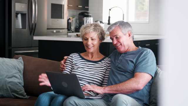 senior couple on the couch at home using a laptop computer - coppia anziana video stock e b–roll