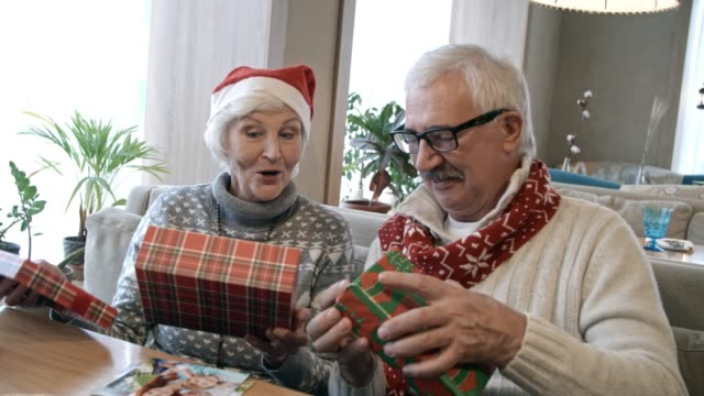Senior Couple Opening Christmas Gifts at Holiday Dinner in Cafe video