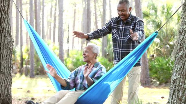 senior couple outdoors, swinging on hammock - oscillare video stock e b–roll