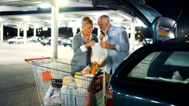 Senior couple packing groceries after shopping. Closeup side view of early 60's couple packing their groceries into their car at a big parking lot next to a supermarket. They are doing their shopping at night. car shopping stock videos & royalty-free footage